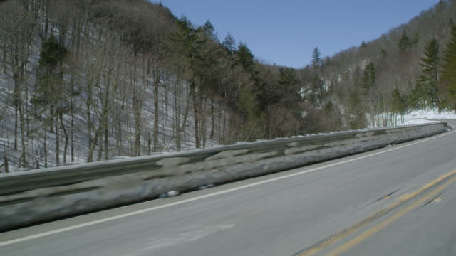 car point of view of mountain road passing through forest during winter - winter点の映像素材/bロール
