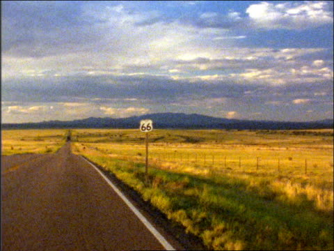 vidéos et rushes de grainy car point of view on country highway on plains past route 66 road sign / mountains in background - route 66