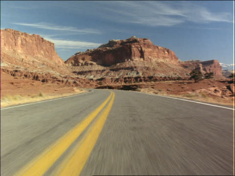 car point of view on country road lined with rock formations - südwestliche bundesstaaten der usa stock-videos und b-roll-filmmaterial