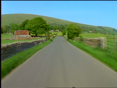 Car point of view on country road through grassy hills / Yorkshire Dales / England