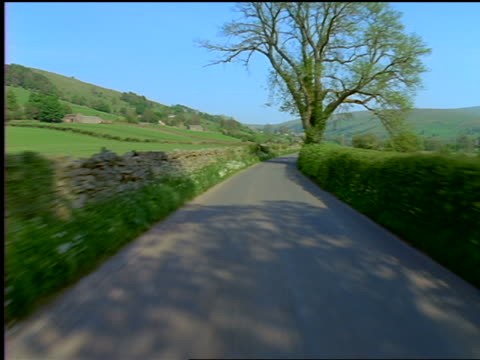 car point of view on country road through grassy hills / yorkshire dales / england - film moving image stock videos & royalty-free footage