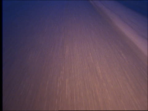Car point of view on mountain highway at dusk / tilt up from close up of road / Austria