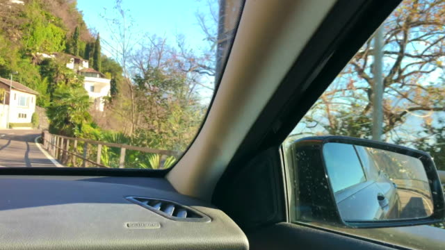 car point of view on mountain road and alpine lake - auto innenansicht stock-videos und b-roll-filmmaterial
