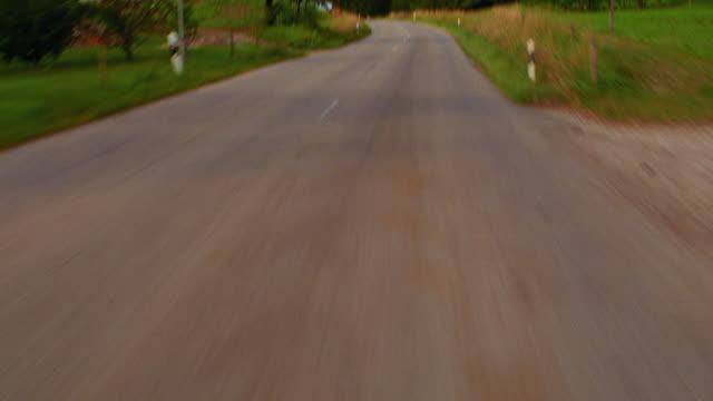 Car point of view on road past group of houses, trees + open field / tilt down tilt up asphalt / Bavaria, Germany