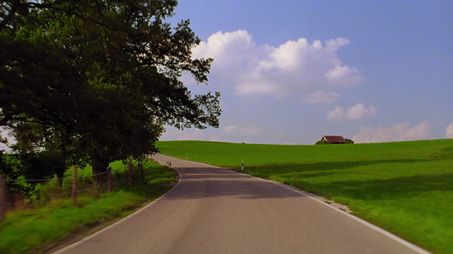 Car point of view on road through countryside past open fields + trees / house in background / Bavaria, Germany