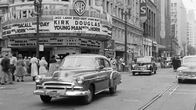 vídeos de stock, filmes e b-roll de b/w 1950 rear car point of view on street passing shops + warner bros movie theater / los angeles - 1950