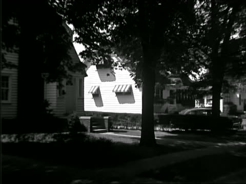 b/w 1949 car point of view on suburban street past woman exiting house - 1949 stock videos & royalty-free footage