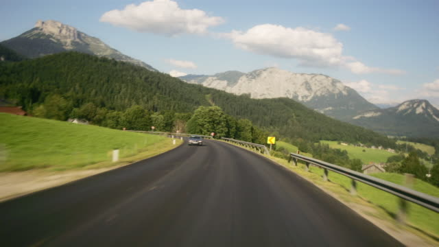 car point of view on winding country road through the town of bad aussee / styria, austria - curve stock videos and b-roll footage