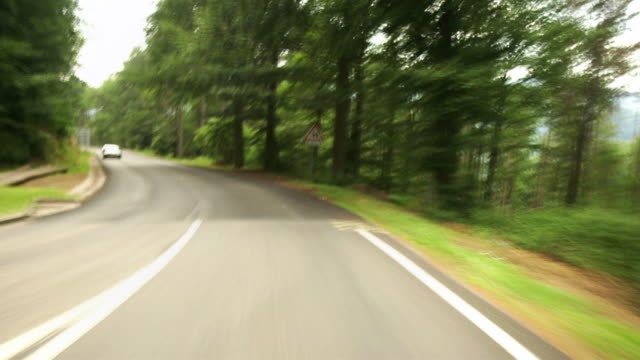 Car point of view on winding road through Parc Naturel Regional des Ballons des Vosges / Alsace, France