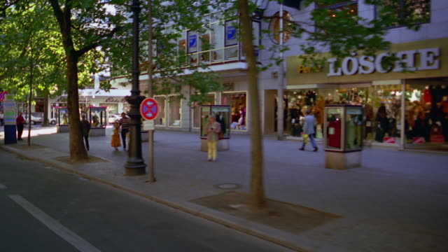 car point of view past people on bicycles, stores + parked tour buses on tree-lined kurfurstendamm (ku'damm) - art stock-videos und b-roll-filmmaterial