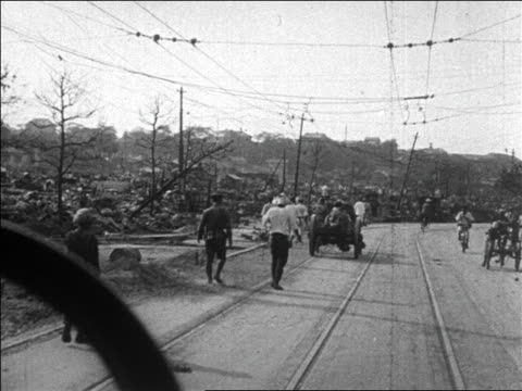 b/w 1923 car point of view past refugees destruction on road after tokyo earthquake / newsreel - 1923 stock-videos und b-roll-filmmaterial
