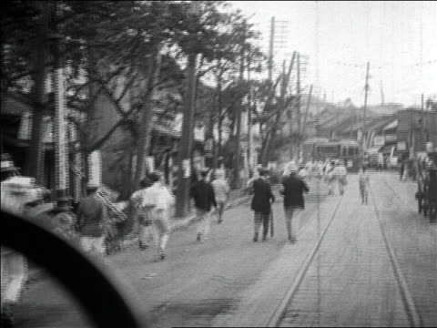 b/w 1923 car point of view past refugees walking on road after earthquake in tokyo / newsreel - 1923 stock-videos und b-roll-filmmaterial