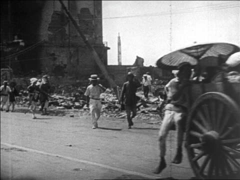 vídeos de stock, filmes e b-roll de b/w 1923 car point of view past refugees walking on road after earthquake in tokyo / destruction in background / news - 1923