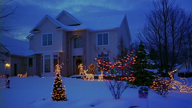 Car point of view past suburban house with Christmas lights at dusk