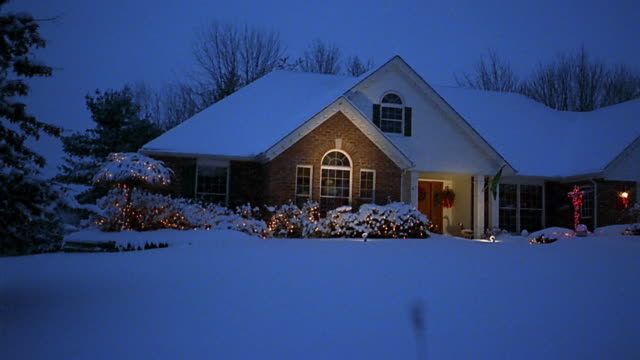 Car point of view past suburban house with Christmas lights in snow at dusk