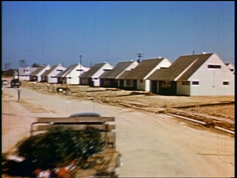 1956 car point of view past truck, suburban houses under construction + construction workers / Levittown, PA