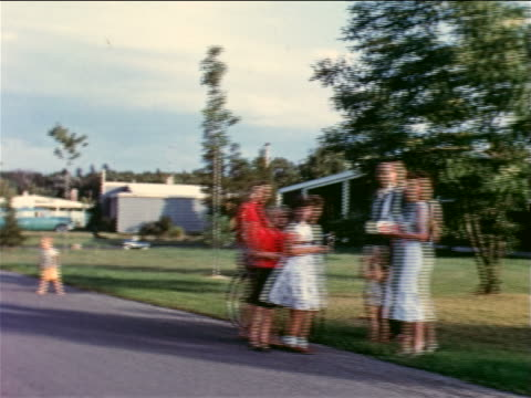1957 car point of view people standing + talking on suburban roadside looking at camera / educational