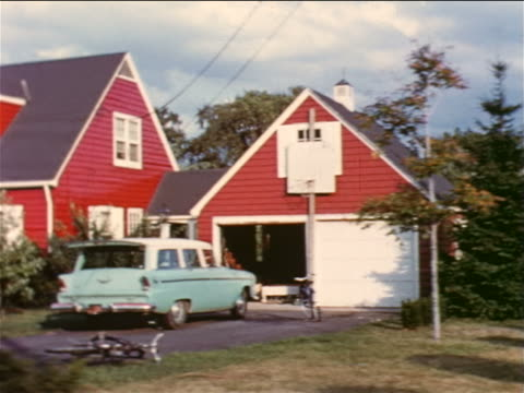1957 car point of view red suburban home with blue station wagon in driveway / educational