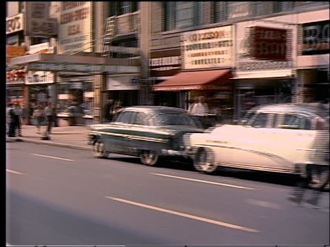 stockvideo's en b-roll-footage met 1956 rear side car point of view shops + movie theaters with people on sidewalk in nyc - 1956