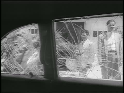 vídeos de stock e filmes b-roll de b/w 1958 car point of view thru broken windows of men standing outdoors / car from nixon motorcade - 1958