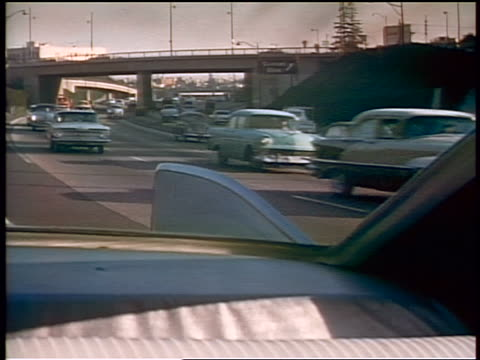 1959 rear car point of view thru windshield of heavy traffic on highway / man at wheel / foot on pedal - 1959 stock videos & royalty-free footage