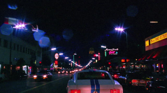 Car point of view time lapse behind traffic on Hollywood Boulevard at night / Los Angeles