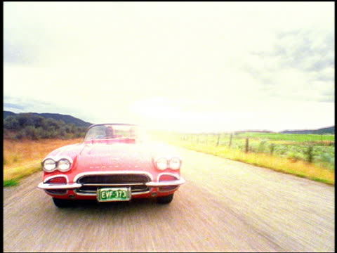 vídeos de stock e filmes b-roll de overexposed rear car point of view time lapse couple driving on country road in 1961 corvette past camera - overexposed