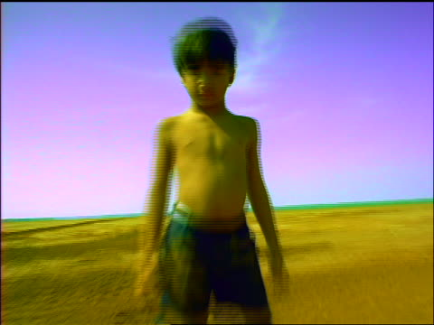 FAST SHAKY car point of view towards + away from shirtless boy standing in desert looking at camera / Panama