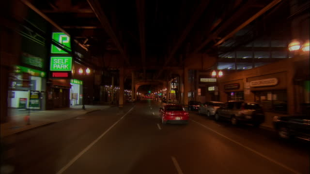 Car point of view under elevated train tracks on Wells Street / Chicago, Illinois