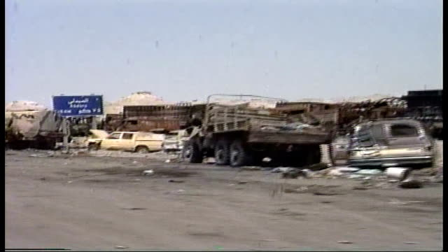 car pov along highway 80, known as the highway of death; destroyed tanks, trucks and other vehicles, belonging to iraqi forces pushed to the side of... - pushing video stock e b–roll