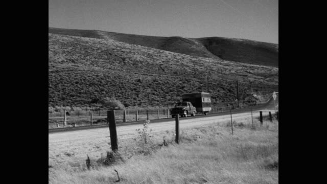 1955 car pulling camper trailer on desert road passing by commercial sign, usa - 1950 stock videos & royalty-free footage