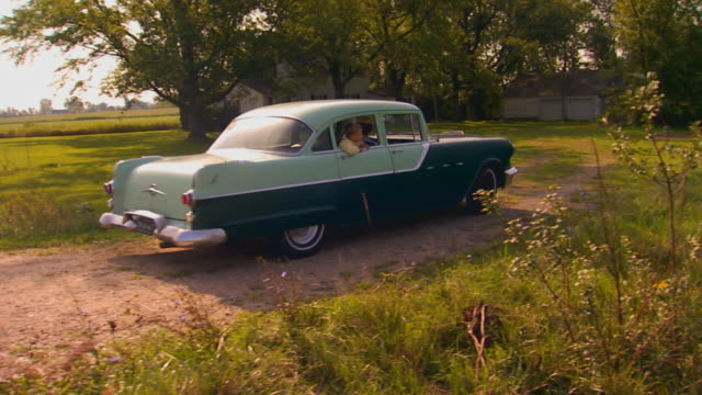 car pulling into dirt driveway, 1950's shot - collector's car stock videos & royalty-free footage