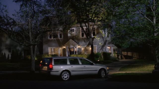 ws car pulling into driveway in front of large home at night / united states - driveway stock videos & royalty-free footage