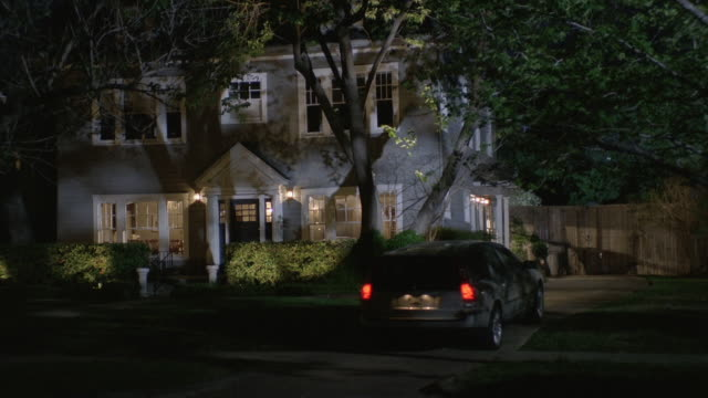 ws car pulling into driveway in front of large home at night / united states - pulling stock videos & royalty-free footage