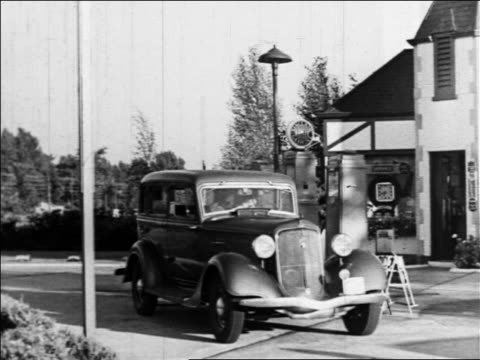 1938 car pulling into gas station / male gas station attendant approaching + bending over car - gas station attendant stock videos and b-roll footage