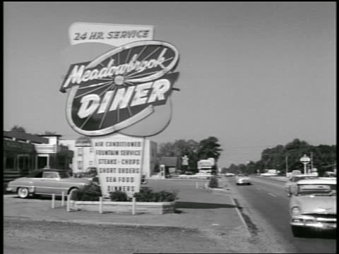 stockvideo's en b-roll-footage met b/w 1955 car pulling into meadowbrook diner / industrial - 1955