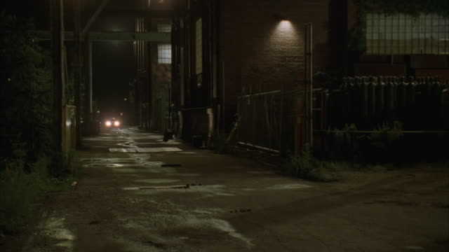 cs, car pulling into warehouse at night  - lagerhalle stock-videos und b-roll-filmmaterial