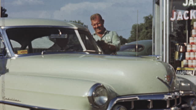 1956 ms car pulling up at cities service gas station, attendant washing windshield / usa - strofinare lavare video stock e b–roll