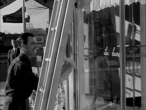 stockvideo's en b-roll-footage met car pulls stops at newsstand, get get out and grabs newspaper / various shots of man washing store window, of bus passengers seen through bus... - metro passagierstrein