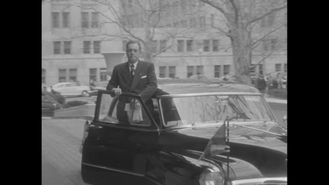 Car pulls up to sidewalk outside Constitution Hall with man standing out of open front passenger side door / Queen Juliana of the Netherlands decars...