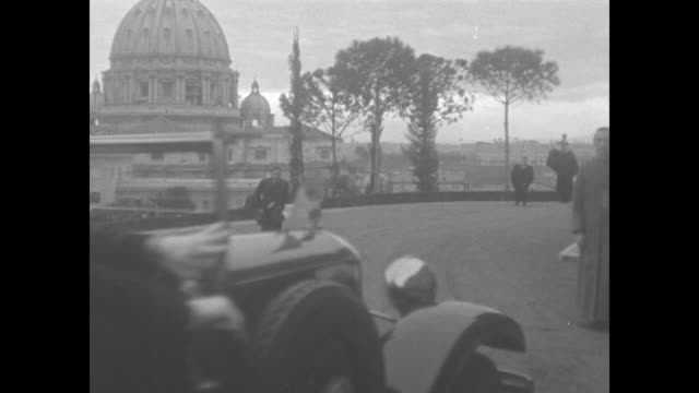 car pulls up to vatican radio station door / priest jumps off car to open door / other priests kneel as pope pius xi exits car / guglielmo marconi... - swiss guard stock videos and b-roll footage
