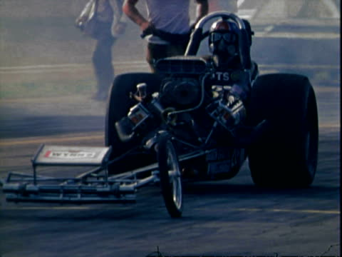 car pushing patriotic top fuel dragster along alley near spectator stands toward drag strip at supernationals ontario motor speedway / driver don... - squirting stock videos and b-roll footage