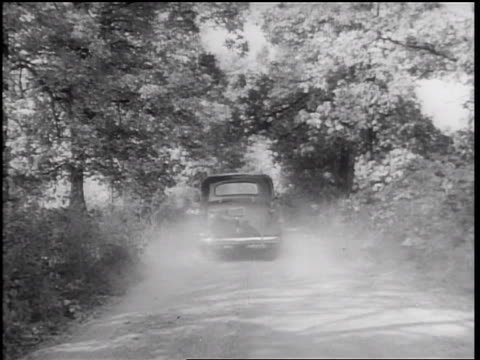 stockvideo's en b-roll-footage met b/w 1938 rear view car raising dust driving on country road away from camera - 1938