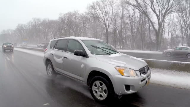 Car POV/Rear POV Vehicles navigate slippery roads on the Northern State Parkway during a Long Island snowstorm