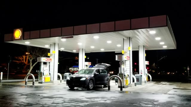 a car refuels at a brightly lit shell gas station at night in dublin california march 12 2018 - petrol station stock videos & royalty-free footage