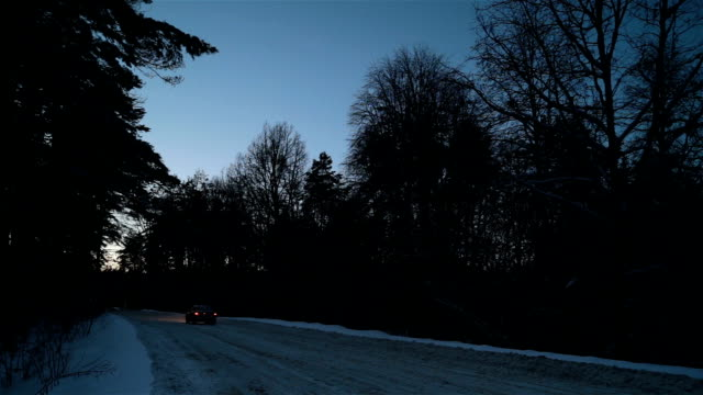 Car rides through winter road in the evening.