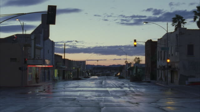 ws car riding on small town street at dusk, usa - abwesenheit stock-videos und b-roll-filmmaterial