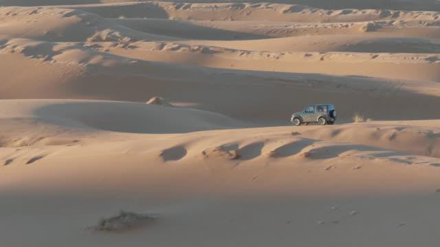 vídeos de stock e filmes b-roll de car riding over the sahara dunes - carro 4x4