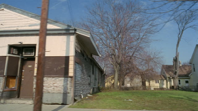side pov car riding through abandoned residential district, rochester, new york, usa - povertà video stock e b–roll