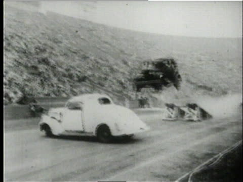 1950 ts car running up a ramp and jumping over another car before crashing / united states - attrezzatura video stock e b–roll